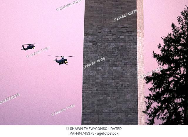 Marine One, right, with United States President Barack Obama aboard, flies near the Washington Monument on approach to the South Lawn of the White House in...