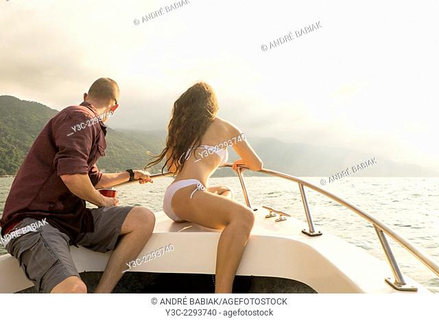 Young couple in swimwear sitting at the front of a fishing boat watching the scenery at the Pacific coastline of Banderas Bay, Mexico