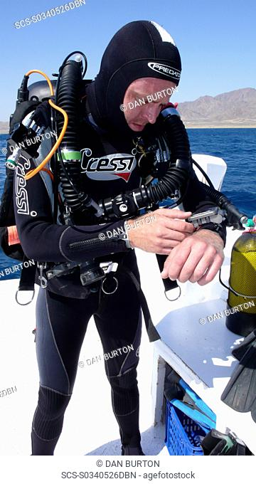 Diver on board dive boat checking equipment