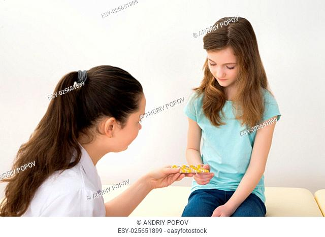 Young Doctor Giving Medicines To Patient Sitting On Bed