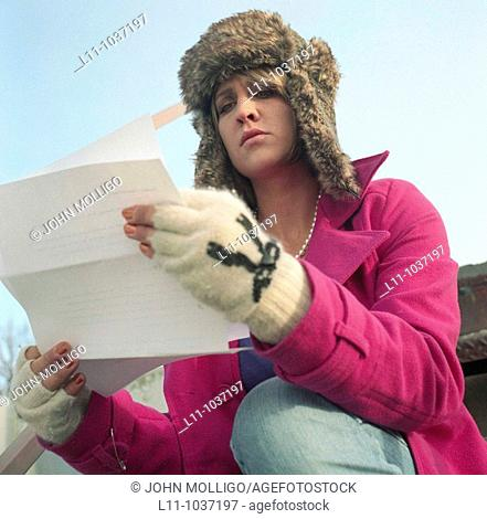 Woman in pink coat and ushanka, reading letter