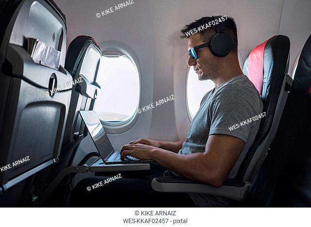 Man in airplane, using laptop, headphones
