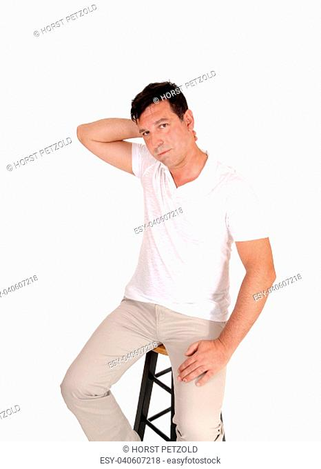 A handsome middle age man sitting on a chair with one hand behind his.head looking very serious, isolated for white background