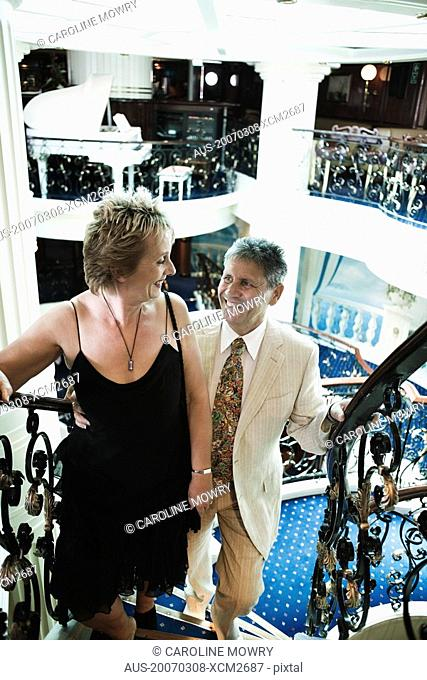 Mature woman and a senior man moving up on a staircase of a ship