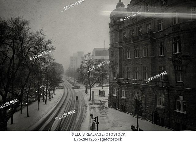Una calle con edificios, gente, trafico etc. una tarde de invierno nevando. Berlin, Alemania, Europa