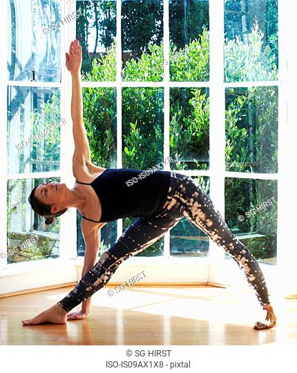 Woman doing yoga in studio, in triangle pose position