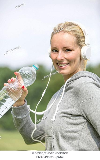 Pretty woman doing sport in park drinking water and smiling at camera