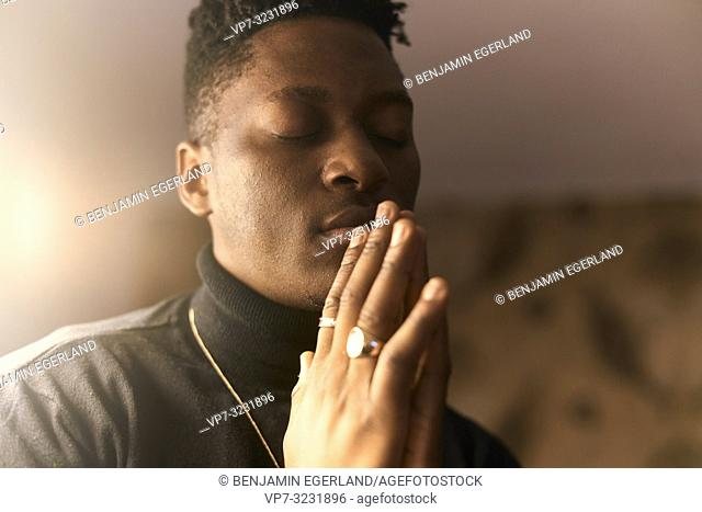young emotional man with closed eyes and folded hands, indoors at home, in Munich, Germany