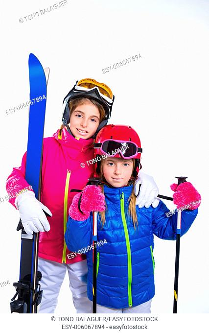 siters kid girls with ski poles helmet and goggles going to winter snow