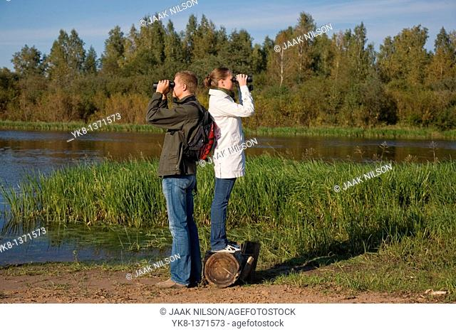 Young couple birdwatching with binoculars by river water