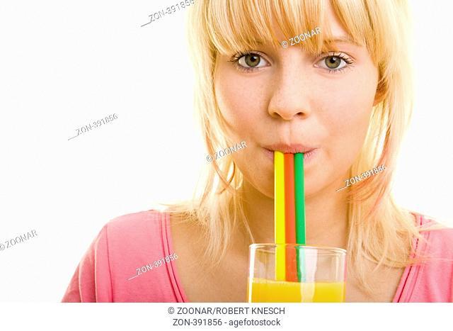 Junge blonde Frau trinkt Orangensaft mit drei bunten Strohhalmen