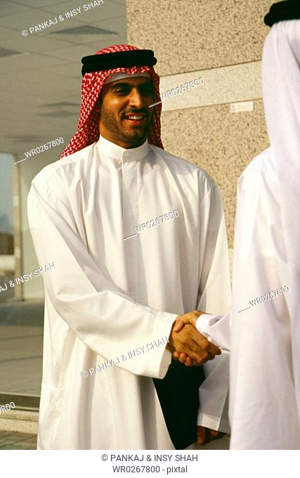 Two Arabs greet each other outside the commercial building