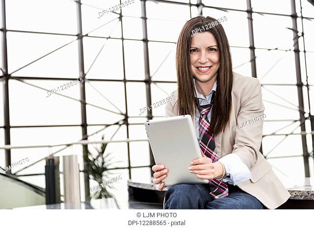 Portrait of a mature business woman with a tablet in the atrium of an office building; Edmonton, Alberta, Canada