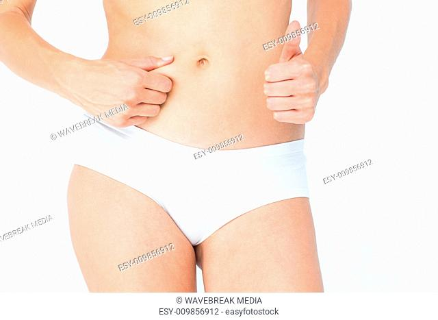 Woman with little fat on her belly with thumb up