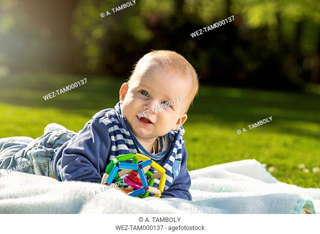 Portrait of smiling baby boy lying on blanket on a meadow