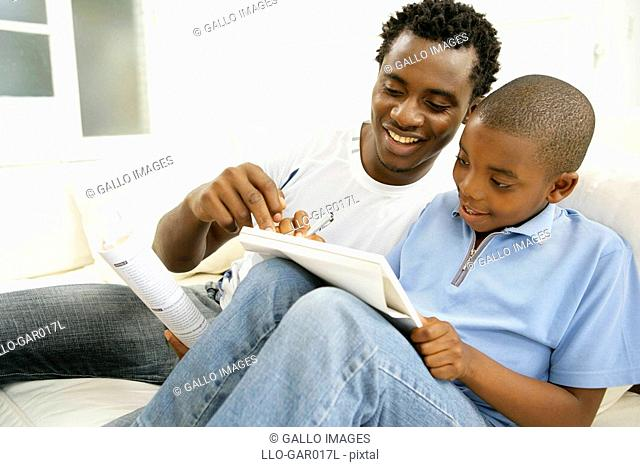 Young African Boy Writing with his Father  Cape Town, Western Cape Province, South Africa