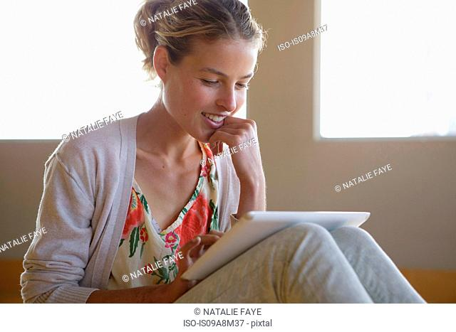 Young woman sitting on floor looking at digital tablet