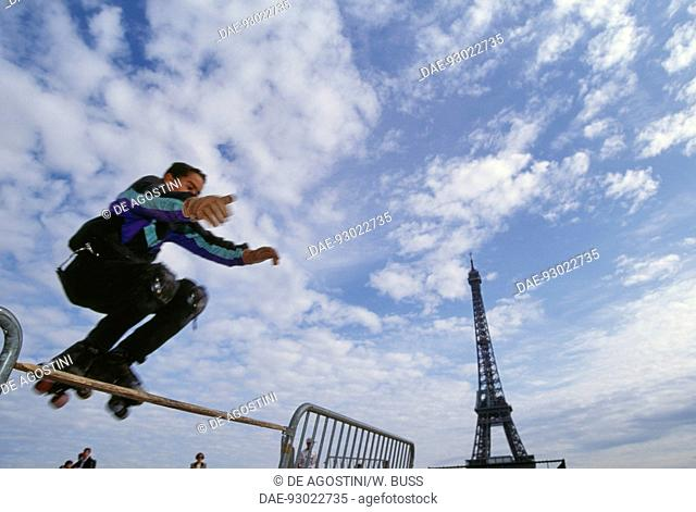 Boy wearing roller skates jumping a hurdle, with the Eiffel Tower in the background, Jardins du Trocadero, Paris, France