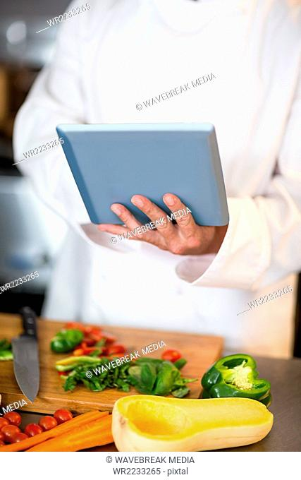 Chef preparing vegetables at counter with tablet
