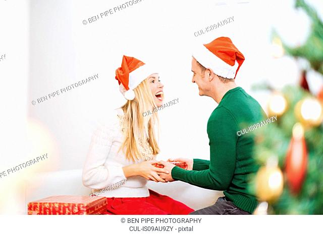Young man handing christmas present to happy girlfriend