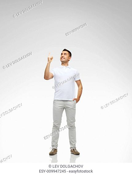 happiness, gesture and people concept - smiling man pointing finger up over gray background