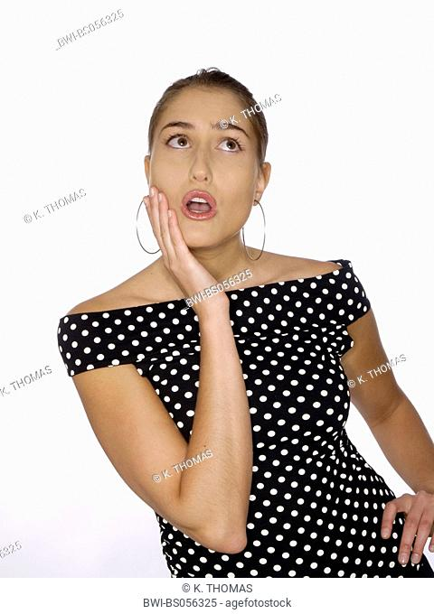 young woman / twen, wearing a dotted blouse, looking shocked