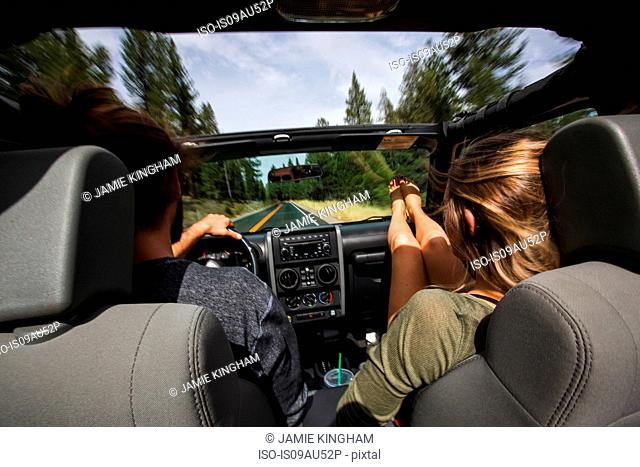 Rear view of young couple on the road in jeep