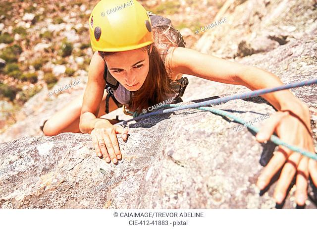 Focused, determined female rock climber