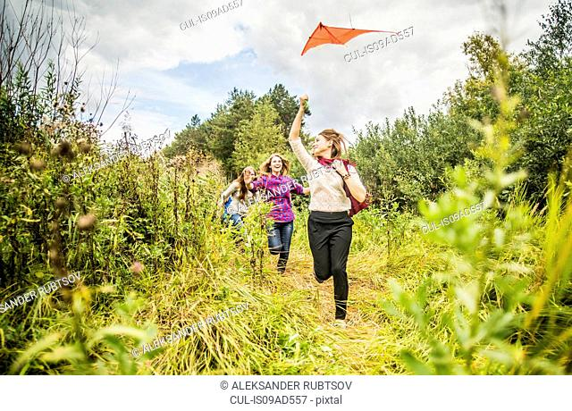 Four young women running through scrubland with kite