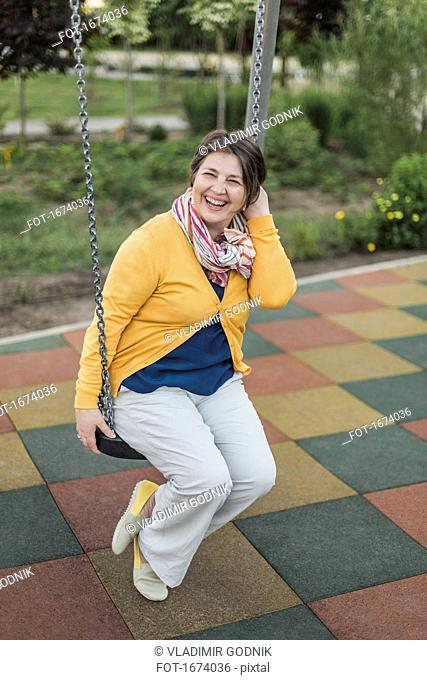 Happy senior woman enjoying on swing at playground