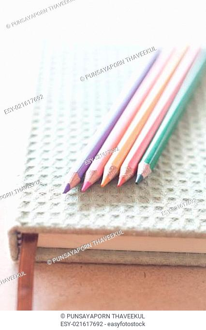 Closeup color pencils on green notebook