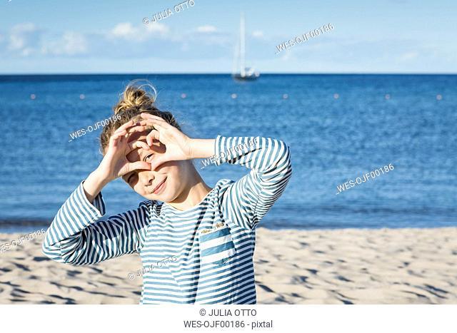 Girl on the beach looking through finger frame