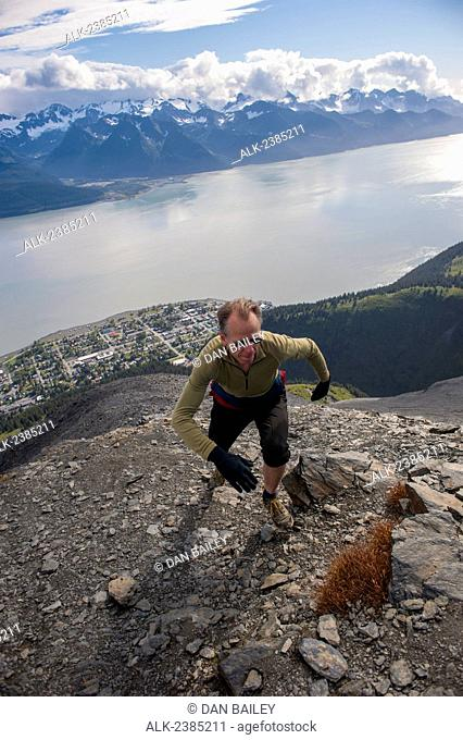Man tops out on the summit ridge of Mount Marathon trail, above Seward, Southcentral Alaska, Summer