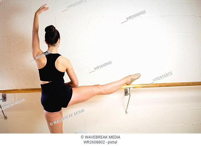 Ballerina stretching on a barre while practising ballet dance