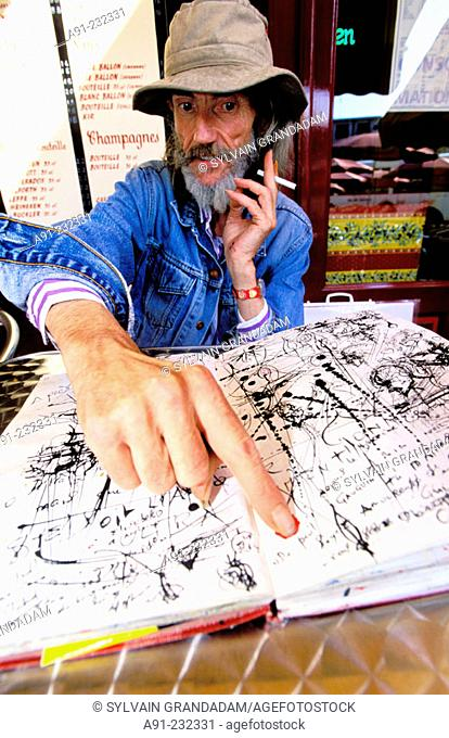 Artist Michel Gauthier pointing out one of his drawings on a book. Avignon. Vaucluse. France