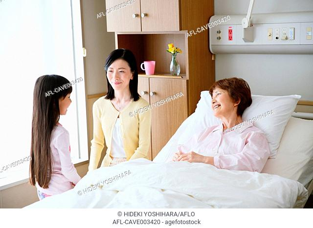 Hospitalized senior Japanese woman with her family