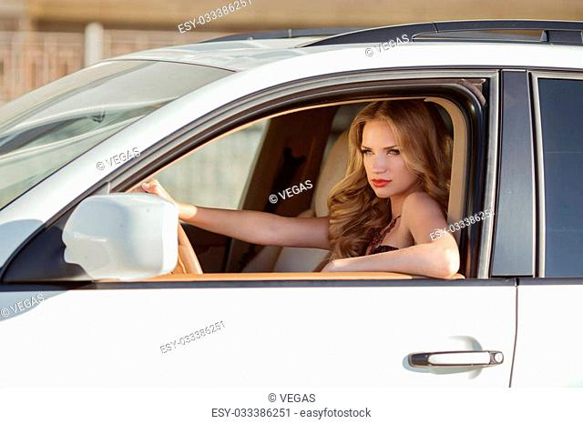 Beautiful driver woman in car indoor keeps wheel looking into the distance