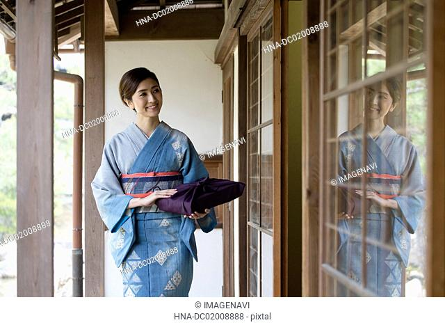 Young Japanese woman in kimono walking on wooden porch