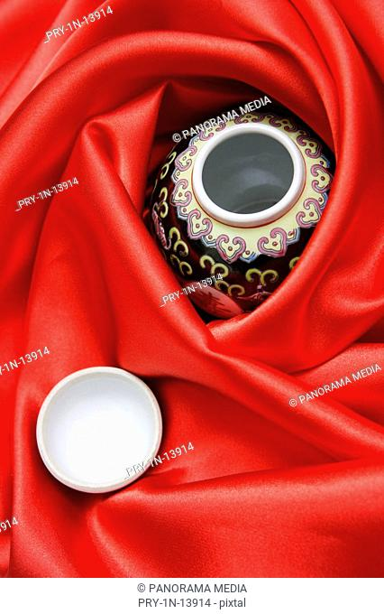 Still life of red silk and porcelains