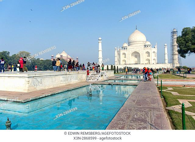 Tourists walk along gardens and large pools of clear water that leads to the Taj Mahal tomb, located in Agra, India