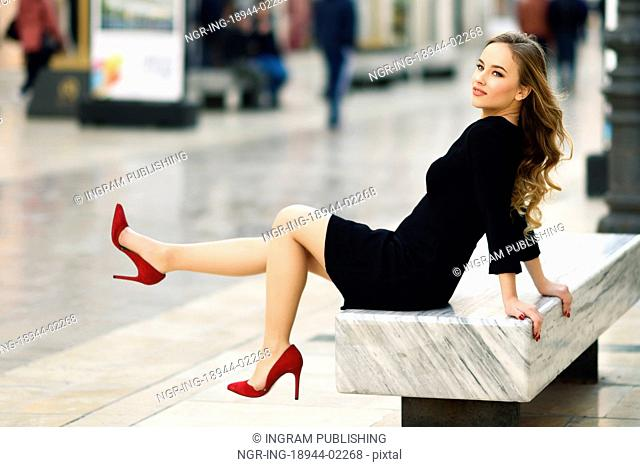 Funny blonde woman with beautiful legs in urban background. Beautiful young girl wearing black elegant dress and red high heels sitting on a bench in the street