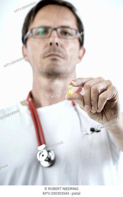 Male doctor showing a capsule of dietary supplement, Bavaria, Germany