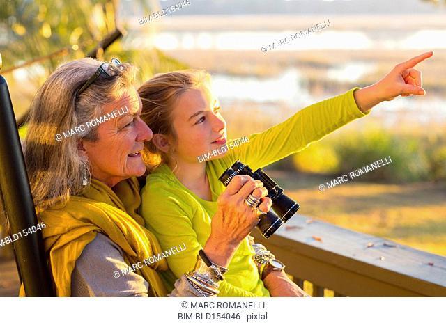 Caucasian grandmother and granddaughter using binoculars on porch