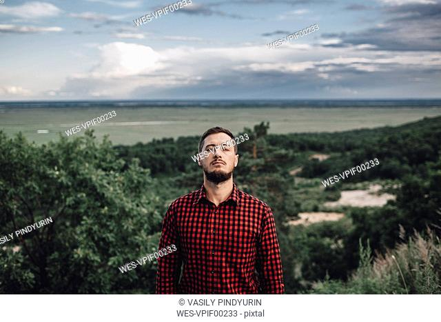 Man with closed eyes in rural landscape