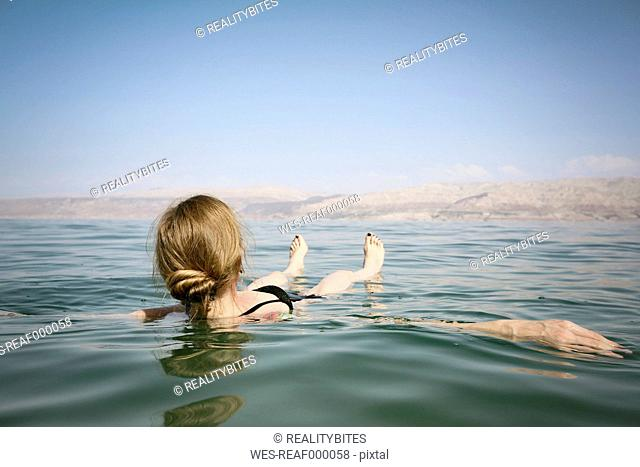Israel, woman floating on water of the Dead Sea