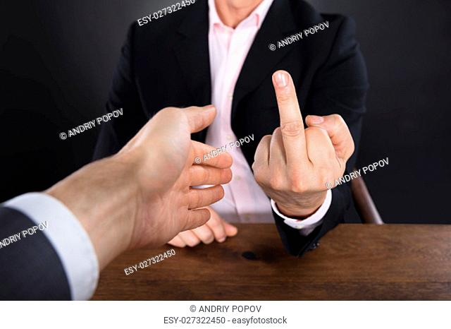 Close-up Of A Businessman Showing Middle Finger To A Partner Offering Handshake On Gray Background