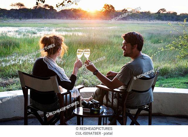 Couple making wine toast at sunset at safari lodge, Kafue National Park, Zambia