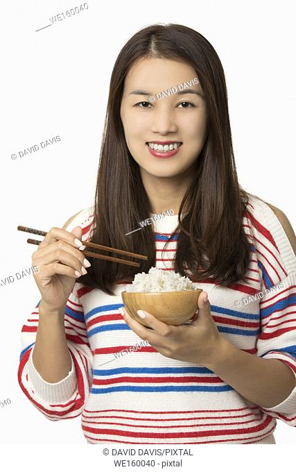 Beautiful Asian American woman eating a bowl of rice isolated on a white background