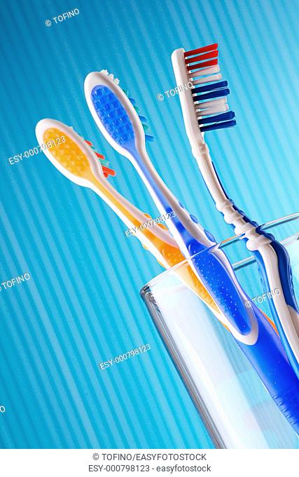Composition with three toothbrushes on blue background