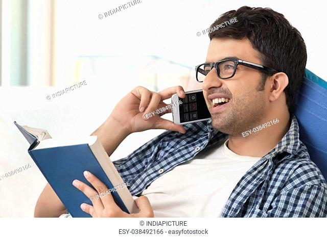 Smiling young man talking on phone while reading book